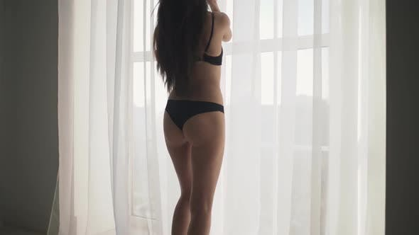 Thumbnail for Sweet Young Sensual Woman with Long Brown Hair Posing in Lingerie Near Big White Window