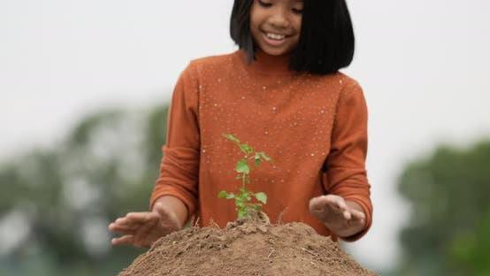 Mädchen pflanzt jungen Baum