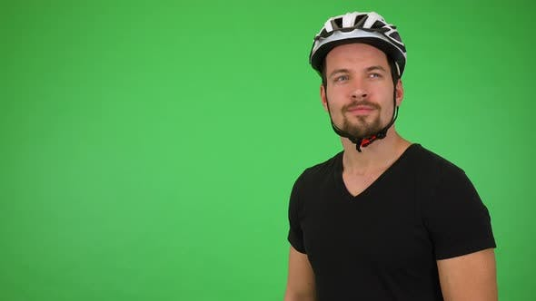 Thumbnail for A Young Handsome Cyclist Looks Around with a Smile - Green Screen Studio