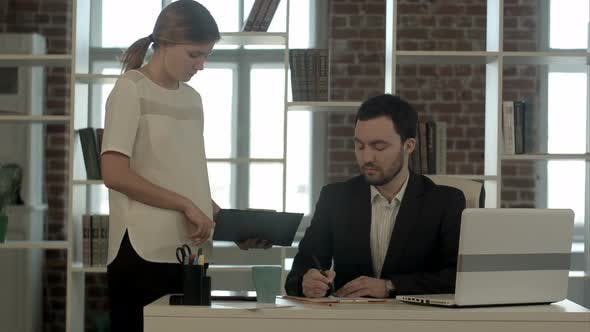 Image of Businesswoman  Pointing Document To Businessman   for Signature  at the Office