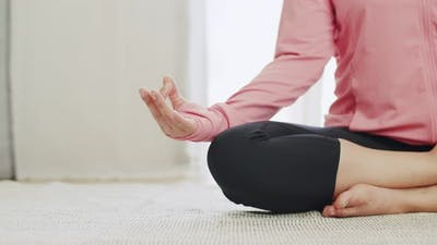 Close-up attractive Asian female practicing yoga meditating.