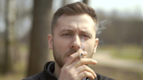 Thumbnail for Person Lighting Up And Smoking Cigarette Outdoor