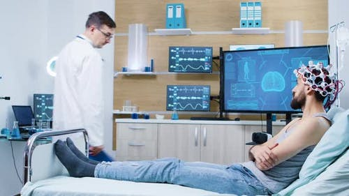 Doctor in a Brain Research Laboratory Checking on Patient Sitting on Bed