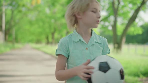 Middle Shot of Cute Blond Boy with Soccer Ball Yelling at Joyful Sister Running Around. Dissatisfied