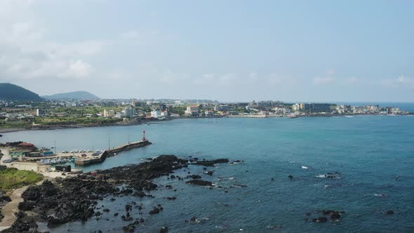 The scenery of a small port village with a blue sea and sky spread out. Jeju