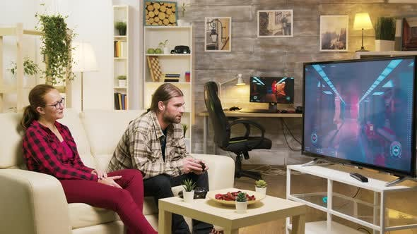 Thumbnail for Cheerful Girlfriend Talking with Her Boyfriend While He's Playing Video Games