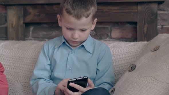 Blonde Junior Schoolboy Surfs Aufmerksam Internet am Telefon