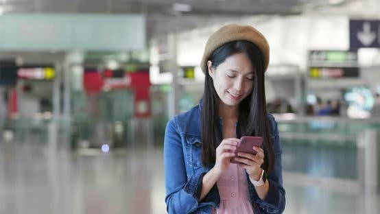 Thumbnail for Woman search on mobile phone in the station