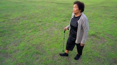 slow-moiton of senior woman walking with walking stick in the grass field