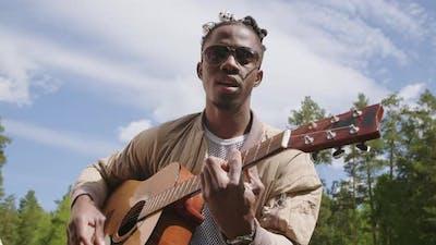 Black Man Singing To Guitar