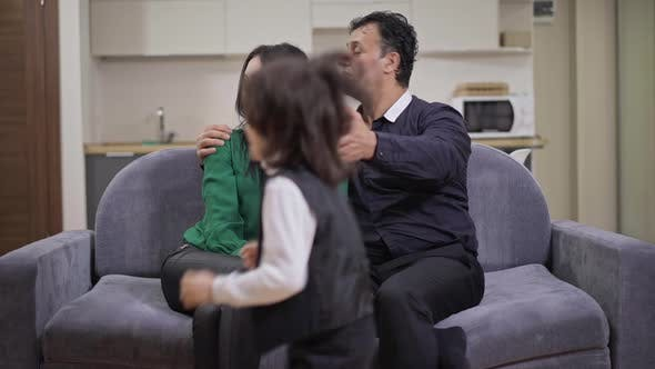 Tired Exhausted Middle Eastern Man and Caucasian Woman Sitting on Couch Talking Hugging As