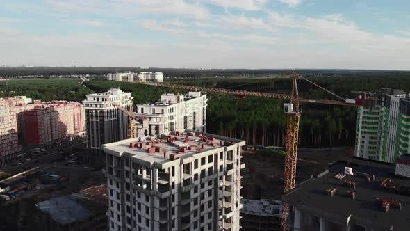 Construction site with cranes and builders of modern residential complex