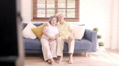 Asian elderly couple watching television in living room at home, sweet couple enjoy.