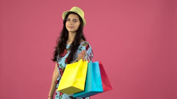 Thumbnail for Girl Posing on Camera with Shopping Bags and Smiling. Pink Background. Slow Motion