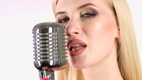 Thumbnail for Singer Sings in a Retro Microphone. White Background. Side View. Close Up