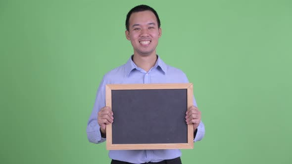 Thumbnail for Happy Asian Businessman Holding Blackboard