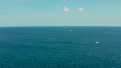 Tourists on a Parachute Over the Sea
