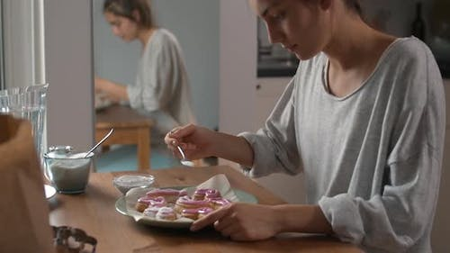 Woman Pouring Powdered Sugar on Cookies