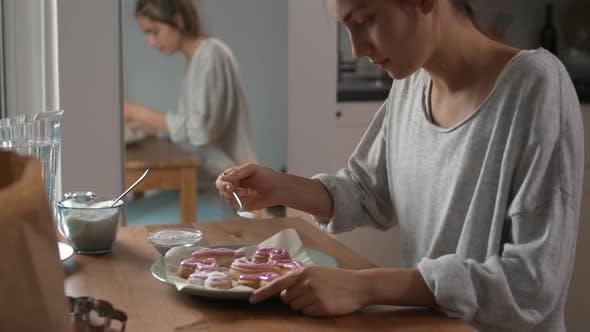 Frau gießt Puderzucker auf Kekse