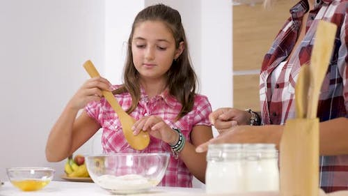 Daughter Helping Her Mother at the Kitchen