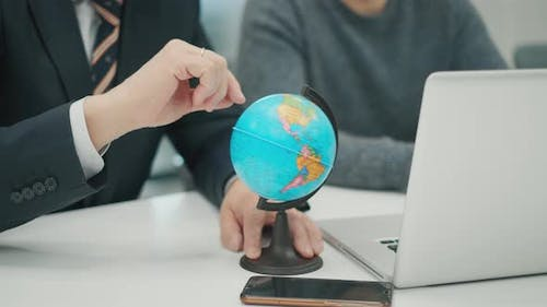 Senior Man CEO at a Business Meeting with a Colleague. Hand Rotates the Globe