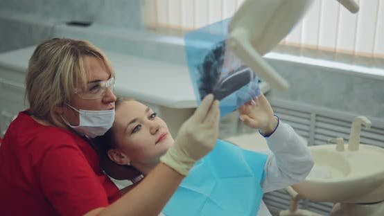 Pretty Woman Dentist Looks at the Patient's X-ray and Tells How the Teeth Will Be Treated