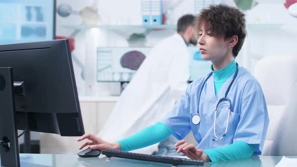 Cover Image for Young Nurse Typing on Computer Keyboard