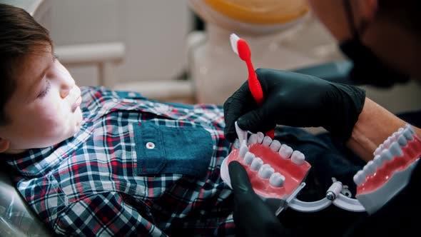 Thumbnail for A Little Boy Having a Treatment in the Dentistry - Explains the Importance of Hygiene Using the