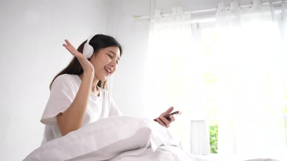 Lovely girl listening to music with headphones in bedroom.