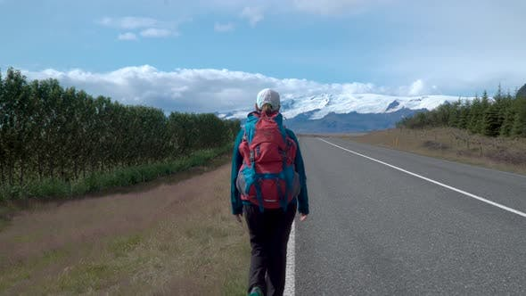 Thumbnail for Woman Traveler with a Backpack Is on an Asphalt Road