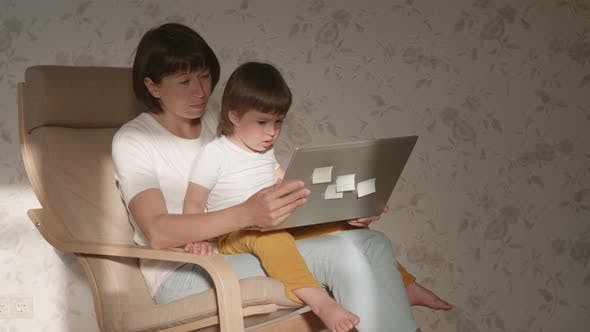 Thumbnail for Mother and Her Toddler Boy Sit Together on Chair with Laptop. Woman Tries To Remote Work, but Kid Is