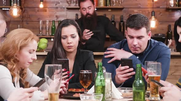 Thumbnail for Modern Day`s Problem: Friends in a Pub Are All Looking Into Smartphones Instead of Talking To Each