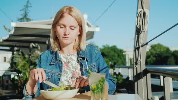 A Young Woman Is Eating a Salad on the Summer Terrace in a Restaurant