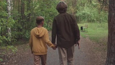 Dad And Son Walking In Forest