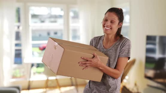 Thumbnail for Cheerful young woman at home tossing shipping box in air excited to open it