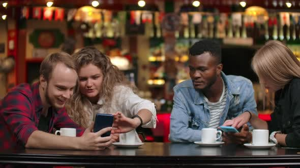 Thumbnail for Multi-ethnic Couples Sitting in a Cafe Look at the Screens By Phone and Leaf Through Photos in the