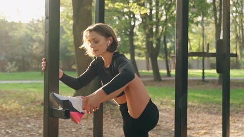 Healthy and Fit Woman Stretching Legs at Park