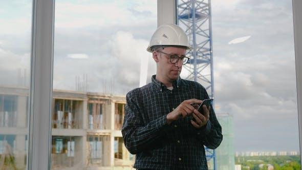 Thumbnail for Engineer using mobile phone in helmet.