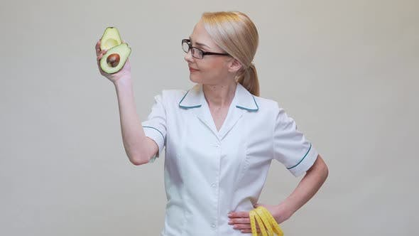 Thumbnail for Nutritionist Doctor Healthy Lifestyle Concept - Holding Organic Avocado Fruit and Measuring Tape