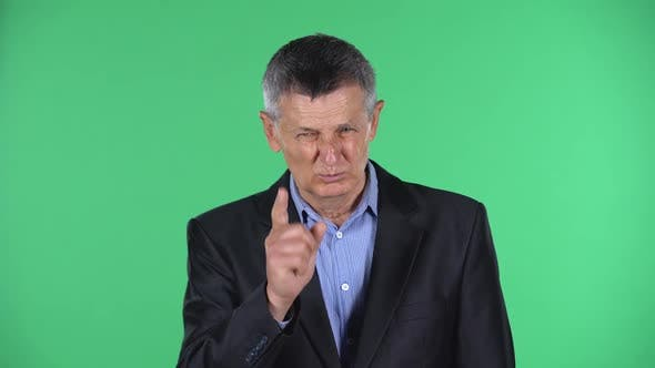 Portrait of Aged Man Is Scolding, Shaking His Index Finger, Isolated Over Green Background