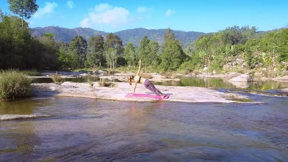 Thumbnail for Flycam Removes From Girl in Yoga Shows River Rapids