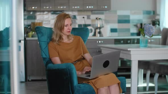 Woman Browsing Website on Laptop at Kitchen