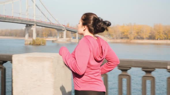 Chubby female doing running workout in industrial city park