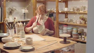 Caucasian Female Ceramics Artist Working on Clay Bowl in Workshop