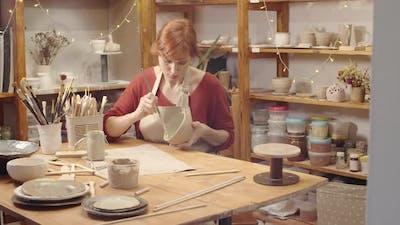 Caucasian Female Ceramics Artist Working on Clay Bowl in Workshop