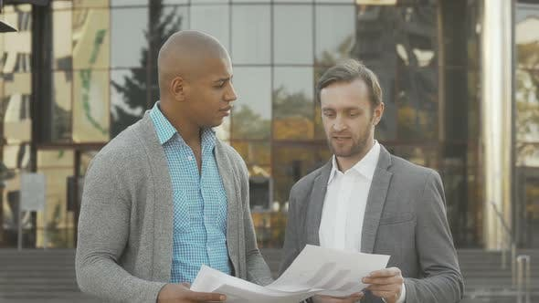 Two Businessmen Examining Documents in Front of Business Building