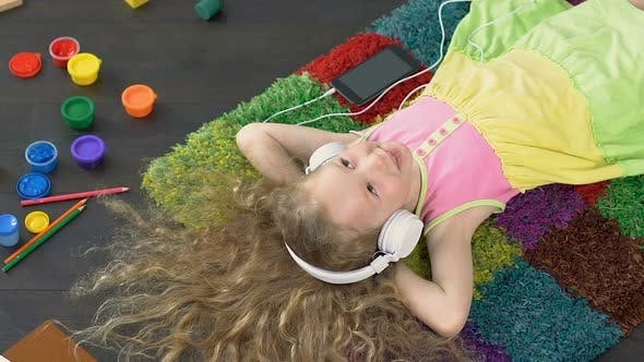 Thumbnail for Young Smiling Girl Singing Favourite Song in Big white Headphones