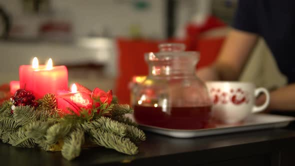 Thumbnail for Christmas Advent Candles on a Table, a Man Drinks Tea and Adds Honey in the Blurry Background