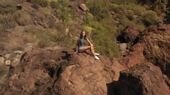Thumbnail for Woman Blowing a Kiss While Sitting on Top of a Rock in Gran Canaria