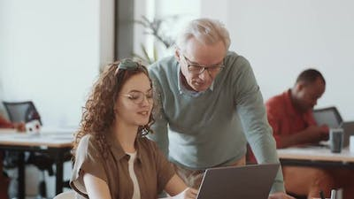 Senior Mentor Talking with Young Cheerful Woman in Office